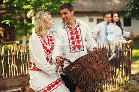 Photo pour Une photo de deux couples debout derrière une vieille maison ukrainienne - image libre de droit