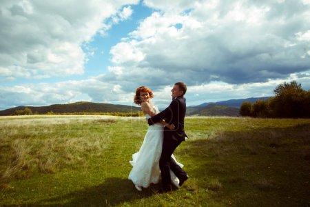 Happy wedding couple dance on the hill under a deep blye sky