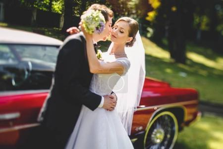 Bride daydreams in the hands of fiance standing behind an old re