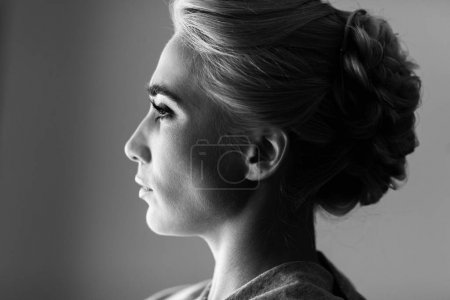 Facial profile of gorgeous blond woman looking out the window