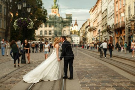 Photo pour Groom embrasse une charmante mariée tandis que le vent souffle sa robe le long des tramways - image libre de droit