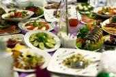 Různé předkrmy ze zeleniny, masa a ryb leží na bílé p