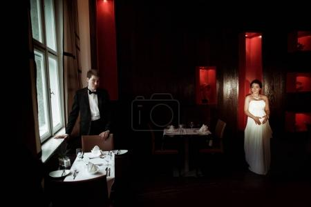 Pregnant bride walks in the cafe to the groom waiting for her