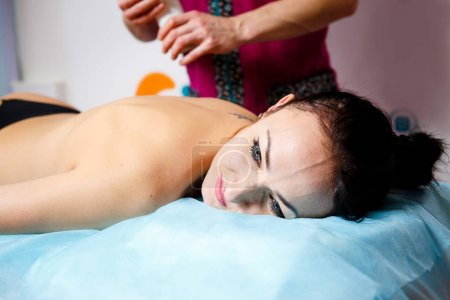 A young male therapist is applying oil to the girl's skin to the patient for Modeling massage and kinesiological muscle testing f for the beautiful body effect