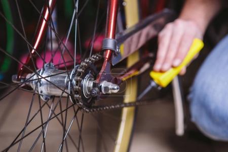 Photo pour Réparation de vélos à thème. Gros plan de la main d'un homme caucasien utiliser un lubrifiant de chaîne dans un lubrificateur jaune pour lubrificateur une chaîne de vélo sur un vélo rouge . - image libre de droit