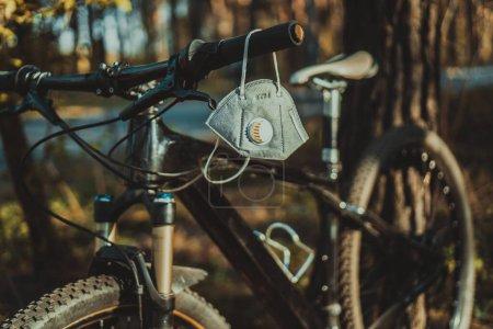 Protecteur masque respirateur jetable au carbone adapté pour protéger contre les particules de brouillard de fumée de brousse PM2,5. Un respirateur à filtre à charbon est accroché au guidon d'un VTT dans une forêt .