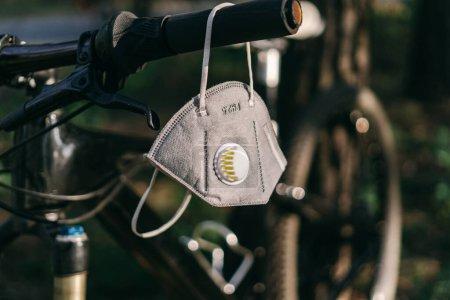 Fermer masque PM2.5 ou masque N95. Pollution atmosphérique pm2.5 concept. Pour la protection pm 2.5 et coronavirus COVID 19. Un respirateur à filtre à charbon est accroché au guidon d'un vélo dans une forêt .