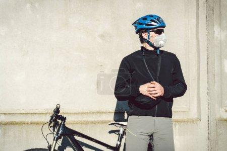 Portrait cycliste masculin près du mur en béton gris dans un respirateur de protection PM 2.5 avec filtre. Protéger les organes respiratoires humains de la poussière et des particules en suspension dans l'air, infection par des maladies infectieuses
