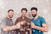 Cheers ! Three cheerful young men with glasses of beer on snowy