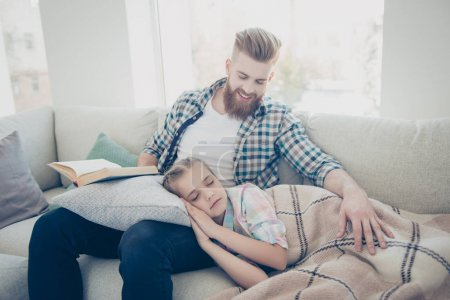 Stylish smiling father with ginger hair sitting on sofa with fai