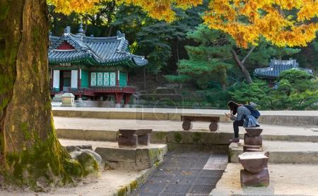 Korean girl sitting at the Pavillion at secret garden of Changde