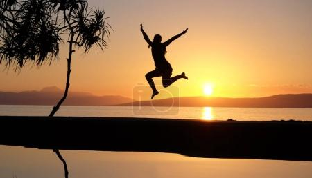 Girl jumping at the waterpool on the beach against the sunset at