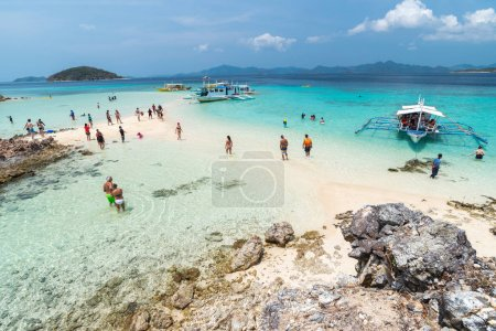 Tropical beach with tourists and boats on the island Bulog Dos