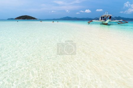 Tropical sandbar with tourists and boats on the Bulog Dos island