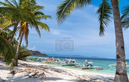 Tropical beach with boats on the Malcapuya Island, Busuanga