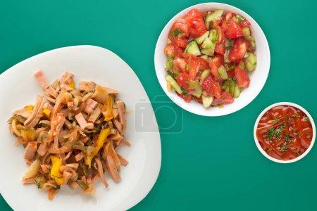 Photo pour Salade berlinoise sur assiette blanche avec salade végétablie sur fond vert. Salade de saucisse, concombre, poivre vue du dessus . - image libre de droit