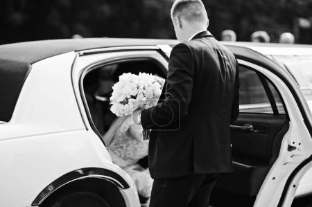 Groom give his hand for bride to take from limousine at wedding