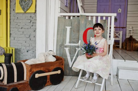Portrait of a cute little girl in a dress sitting on a chair in