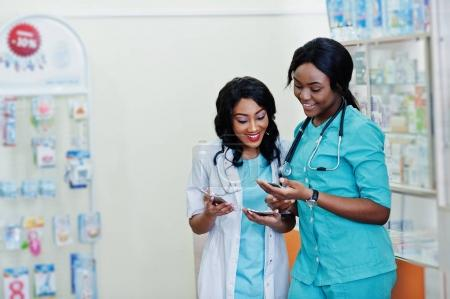 Two african american pharmacist working in drugstore at hospital