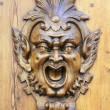 Demoniac face carved on a wooden door of Siena, Tu...