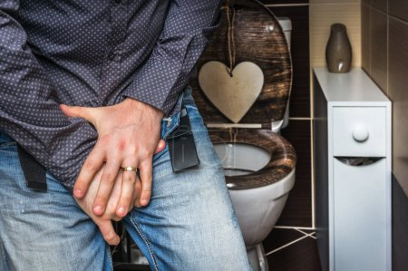 Man with hands holding his crotch - incontinence concept