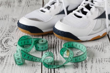 Sport shoes and measure tape on white background.Sport shoes and