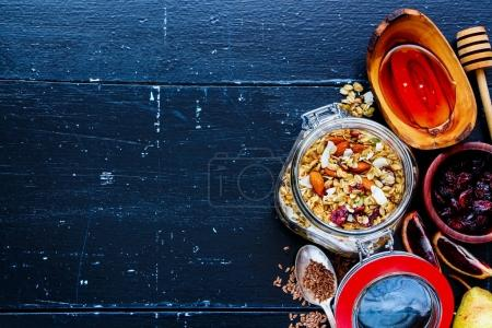 Photo for Glass jar of homemade oatmeal granola with fruits and nuts on dark vintage background. Top view. Flat lay style. Clean eating, vegan, vegetarian, detox and dieting concept - Royalty Free Image