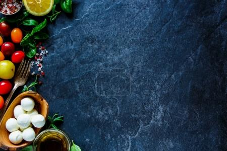 Photo pour Salade de caprese frais ingrédients de tomates cerises, basilic, boules de mozzarella et huile d'olive sur fond de pierre vintage. Concept de cuisine. Vue de dessus. Cuisine italienne . - image libre de droit