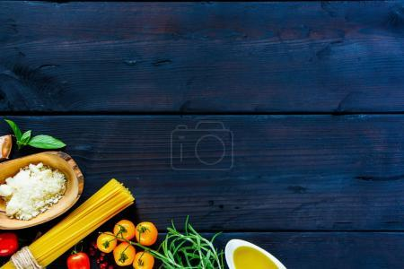 Photo for Pasta cooking concept. Spaghetti with ingredients (rosemary, basil, tomato, olive oil, pepper, parmesan cheese) on a dark wooden table, top view, copy space. Flat lay. Italian food background - Royalty Free Image