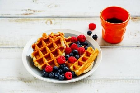 Photo for Close up of breakfast set. Warm homemade traditional belgian waffles with fresh berry and cup of espresso on white rustic wooden background, side view, selective focus. - Royalty Free Image
