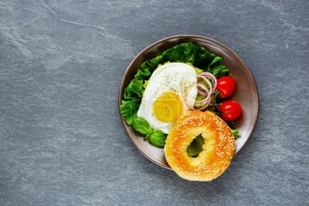 Photo for Healthy vegetarian breakfast plate - bagel with fried egg and fresh vegetables on grey concrete background, top view, copy space. Flat lay. Clean eating, healthy, diet, detox food concept - Royalty Free Image