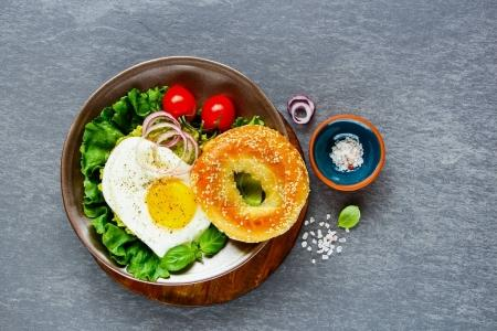 Photo for Flat lay of vegetarian breakfast plate - bagel with fried egg and fresh vegetables over grey concrete background, top view, copy space. Clean eating, healthy, diet, detox food concept - Royalty Free Image
