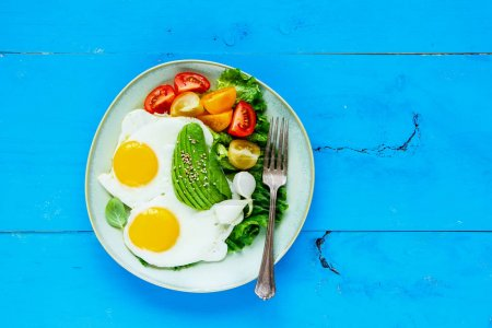 Photo for Healthy vegetarian breakfast plate flat-lay. Fried eggs, avocado and fresh vegetables on blue wooden table, top view, copy space. Clean eating and energy boosting food concept - Royalty Free Image