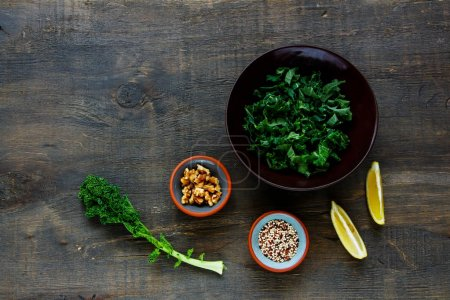 Photo for Healthy ingredients for making raw kale and quinoa salad with feta cheese and walnut on wooden board. Top view. Flat lay. Clean eating, dieting, vegetarian food concept - Royalty Free Image