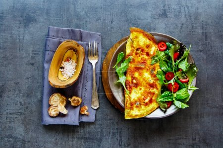 Photo for Flat-lay of delicious mushroom omelette with salad on plate over dark concrete copy space background. Healthy food concept. Top view - Royalty Free Image