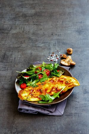 Photo for Mushroom omelette on plate and fresh salad over dark concrete copy space background. Healthy food concept. Side view, selective focus - Royalty Free Image