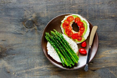 Photo for Healthy veggie breakfast flat lay. Sandwiches with soft cheese, avocado, tomatoes and aspargus on bagels over wooden background. Top view. Weight loss, clean eating, detox food concept - Royalty Free Image