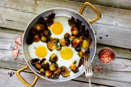 Photo for Brussel sprouts in frying pan with fried eggs on wooden table flat-lay - Royalty Free Image