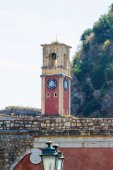 Old Byzantine clock tower on green mountains
