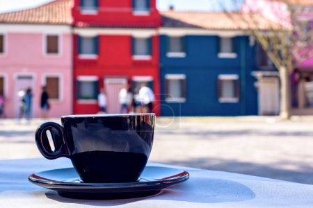 Daylight view to black coffee cup on table and colorful building