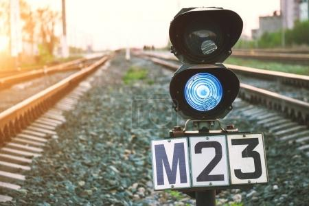 Traffic light shows blue signal on railway. Prohibiting signal. Railway station. Regulation and control of movement. Travel by train.