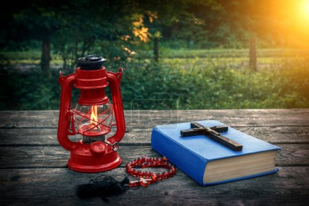 Wooden christian cross on bible, burning kerosene lamp and prayer beads on the old table. Church utensils. Salvation of soul and expiation of sins. Religious confession. In god we trust. Christianity.
