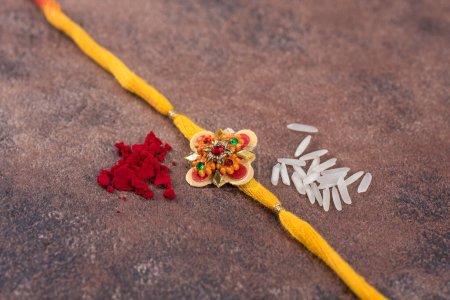 Photo pour Raksha Bandhan : Rakhi avec des grains de riz et kumkum sur fond de pierre, Bracelet indien traditionnel qui est un symbole d'amour entre frères et sœurs . - image libre de droit