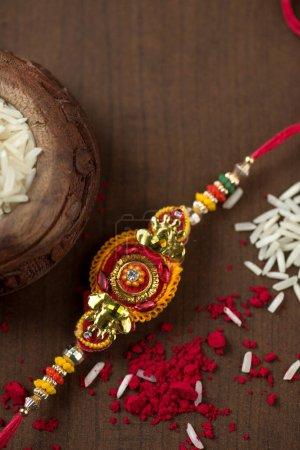 Photo pour Festival indien : fond Raksha Bandhan avec un élégant Rakhi, Rice Grains et Kumkum. Un bracelet traditionnel indien qui symbolise l'amour entre frères et sœurs. - image libre de droit