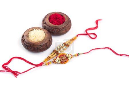 Photo pour Fond Raksha Bandhan avec un élégant Rakhi, Rice Grains et Kumkum sur fond blanc. Un bracelet traditionnel indien qui symbolise l'amour entre frères et sœurs . - image libre de droit