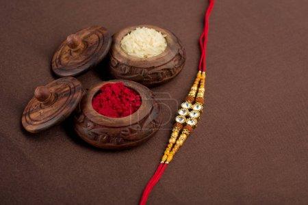 Photo pour Fond Raksha Bandhan avec un élégant Rakhi, Rice Grains et Kumkum. Un bracelet traditionnel indien qui symbolise l'amour entre frères et sœurs . - image libre de droit