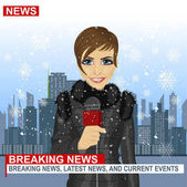 Female journalist working in winter in front of city with skyscrapers holding microphone