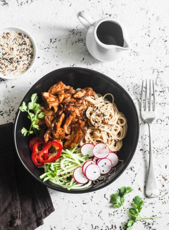 Rice noodles and teriyaki chicken stir fry with quick pickled cucumbers and radishes. On a light background, top view. Asian food style