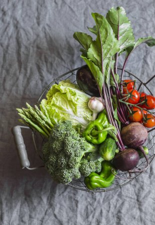 Photo for Food basket with fresh organic garden vegetables - beets, broccoli, eggplant, asparagus, peppers, tomatoes, cabbage on a grey table, top view. Healthy food concept - Royalty Free Image