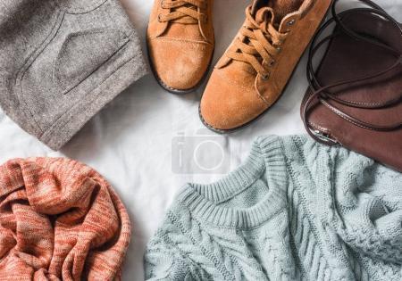 Foto de Ropa conjunto mujer - falda, botas de gamuza, Jersey, bufanda, cuero cruzada cuerpo de la bolsa sobre un fondo claro, la vista superior. Ropa femenina de invierno, otoño - Imagen libre de derechos